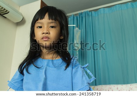 Portrait of a sick girl lying in a hospital bed - stock photo