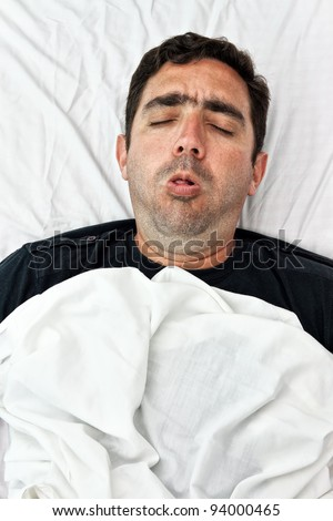 Portrait of a sick hispanic man laying in bed and coughing - stock photo