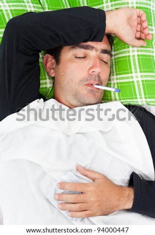 Portrait of a sick hispanic man laying in bed with a thermometer in his mouth and his eyes closed