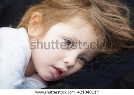 Portrait of a sick little girl in a bed - stock photo