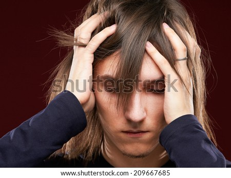 Portrait of a sick man having a migraine , isolated on dark background - stock photo