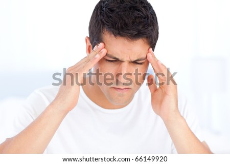 Portrait of a sick man having a migraine sitting in his bedroom - stock photo
