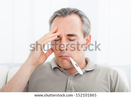 Portrait of a sick man with thermometer in his mouth - stock photo