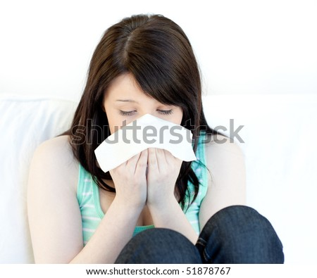 Portrait of a sick teen girl blowing sitting on a sofa - stock photo