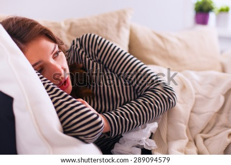 Portrait of a sick woman while sitting on the sofa  - stock photo