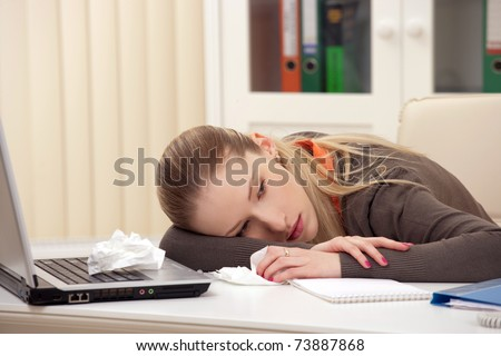 Portrait of a sick young lying on her desk in workplace - stock photo