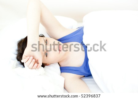 Portrait of a sick young woman lying on her bed at home - stock photo