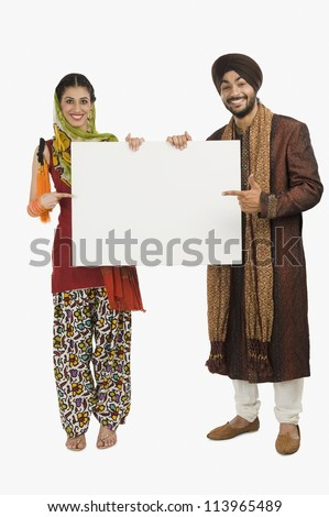 Portrait of a Sikh couple holding a blank placard - stock photo