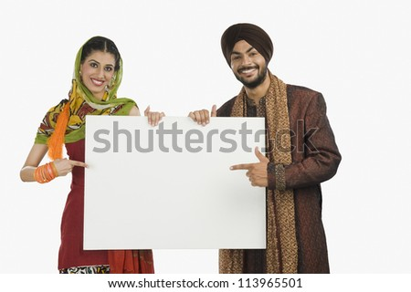 Portrait of a Sikh couple holding a blank placard