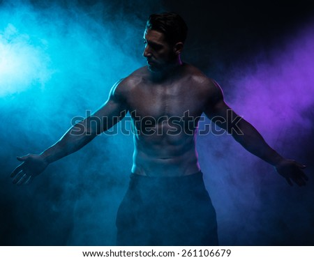 Portrait of a Silhouette Shirtless Muscled Man Posing in the Smoke and Looking at the Camera on a Dark Blue Green Background. - stock photo