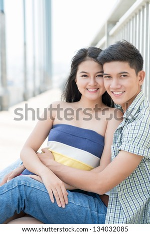 Portrait of a sitting and embracing couple outside - stock photo