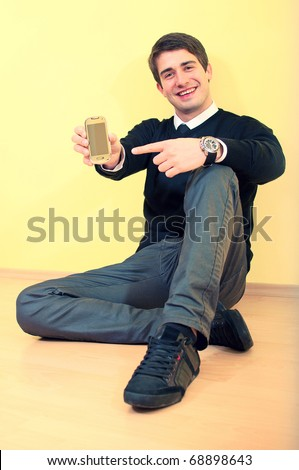 Portrait of a sitting smiling attractive young business man pointing to mobile phone against uniform background - stock photo