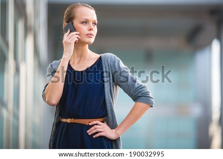 Portrait of a sleek young woman calling on a smartphone in an urban/city context (shallow DOF; color toned image) - stock photo