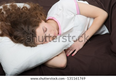 Portrait of a sleeping curly girl in white T-shirt
