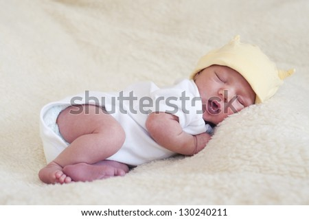 Portrait of a sleeping newborn baby; child is dressed in white vest and yellow hat and is lying on a fur blanket. - stock photo