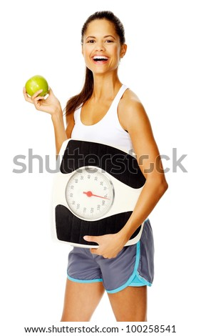 portrait of a slim fitness woman with apple and scale promoting healthy weightloss - stock photo