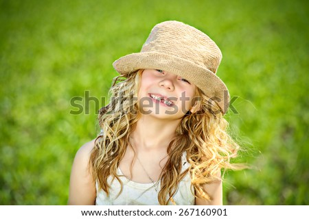 Portrait of a sly little girl in the countryside. Happy childhood. Emotions. - stock photo