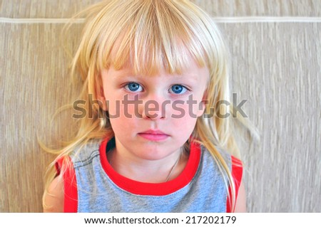 Portrait of a small boy with blonde hair and blue eyes - stock photo