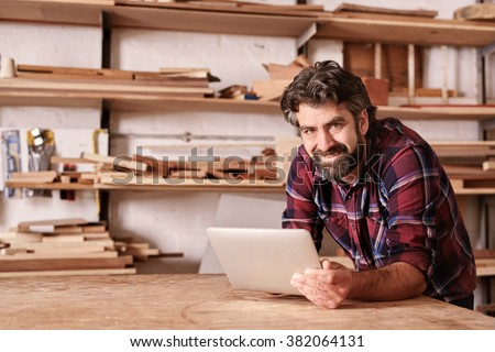Portrait of a small business owner smiling at the camera, resting on his workbench and holding a digital tablet, with shelves of wood behind him in his woodwork studio - stock photo