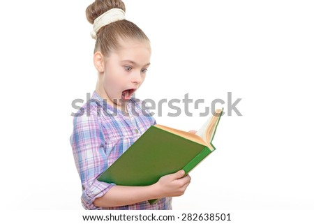 Portrait of a small girl holding a big green book reading it looking very excited with her mouth wide opened wearing colorful checkered shirt with big bun hairstyle ,isolated on a white background - stock photo