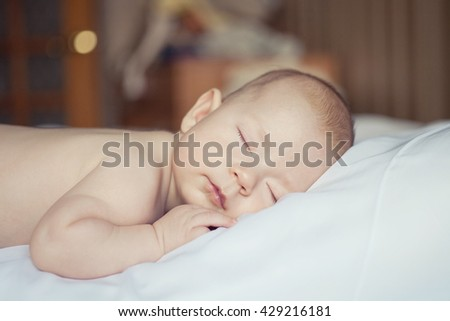 portrait of a small sleeping baby curled up - stock photo