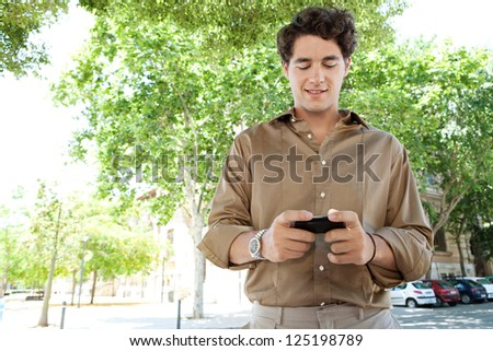 Portrait of a smart businessman using his smart phone in the city, smiling. - stock photo