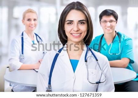 Portrait of a smart female doctor sitting in front of his team and smiling - stock photo