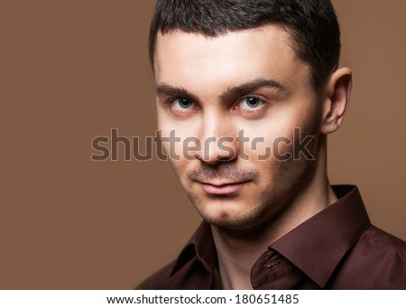Portrait of a smart serious young man standing against brown background