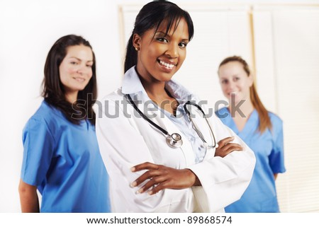 Portrait of a smart young female doctor standing in front of his team and smiling - stock photo