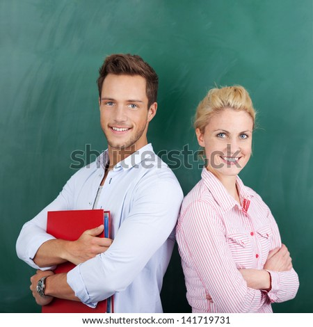 Portrait of a smart young man and woman with binder standing against chalkboard - stock photo