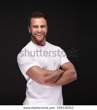 Portrait of a smart young man in white shirt standing with arms crossed against dark gray background - stock photo