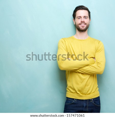 Portrait of a smart young man in yellow shirt smiling with arms crossed - stock photo