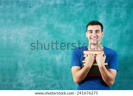 Portrait of a smart young man smiling feeling confident holding stack of books standing against chalkboard . - stock photo