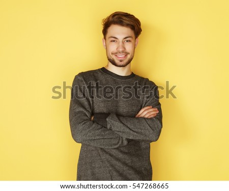 Portrait of a smart  young man standing against yellow backgroun