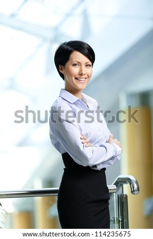 Portrait of a smiley businesswoman with arms crossed wearing white shirt and black skirt at business centre - stock photo