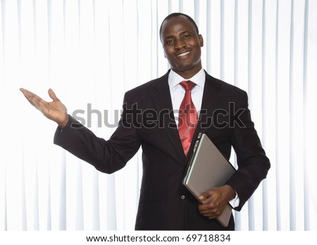 Portrait of a smiling African American business man with a laptop on white background