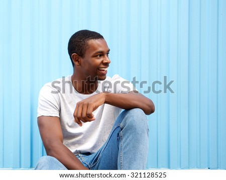 Portrait of a smiling african american man sitting against blue background looking away - stock photo