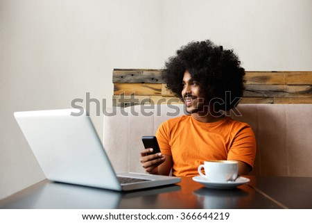 Portrait of a smiling african american man sitting at table with mobile phone - stock photo