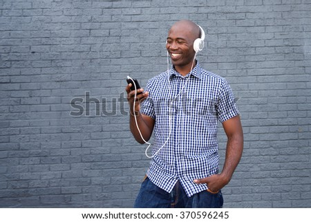 Portrait of a smiling african american with headphones and smart phone - stock photo