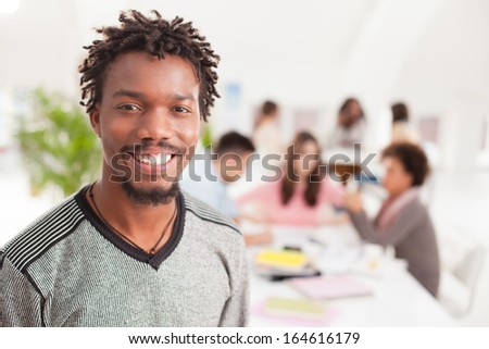 Portrait of a smiling African college student standing in front of his peers. - stock photo