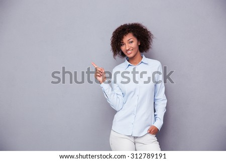 Portrait of a smiling afro american businesswoman pointing finger away over gray background and looking at camera - stock photo