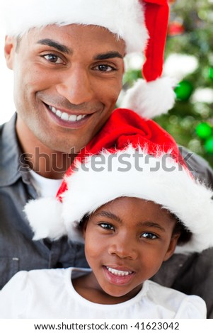 Portrait of a smiling Afro-American father and daughter at Christmas time - stock photo