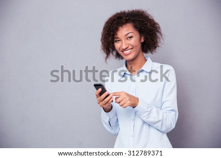 Portrait of a smiling afro american woman using smartphone and looking at camera over gray background - stock photo