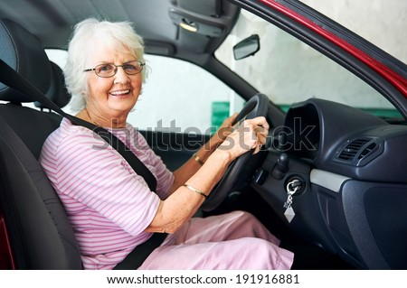 Portrait of a smiling aging woman sitting in a vehicle - stock photo