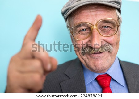 Portrait of a smiling and confident senior good looking business man with finger - stock photo