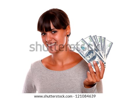 Portrait of a smiling and pretty young woman holding dollars against white background - stock photo