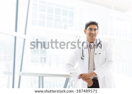 Portrait of a smiling Asian Indian male medical doctor standing inside hospital. - stock photo