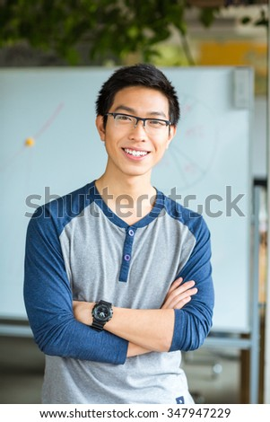 Portrait of a smiling asian male student standing with arms folded in university and looking at camera - stock photo