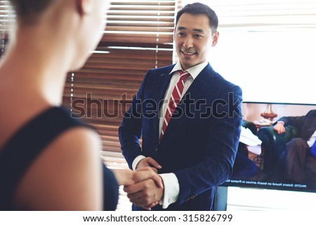 Portrait of a smiling asian men entrepreneur handshake with his female business partner, two successful people congratulate each other shaking hands in honor of the signing of the joint project - stock photo