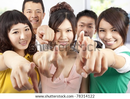 Portrait of a smiling asian students pointing at you - stock photo